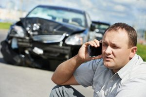 Man on phone ringing insurance company after an accident for repair costs